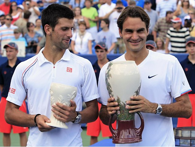 Novak Djokovic, left, from Serbia, and Roger Federer, from Switzerland, pose with their trophies after the men's final at the Western &amp; Southern Open tennis tournament on Sunday, Aug. 19, 2012, in Mas