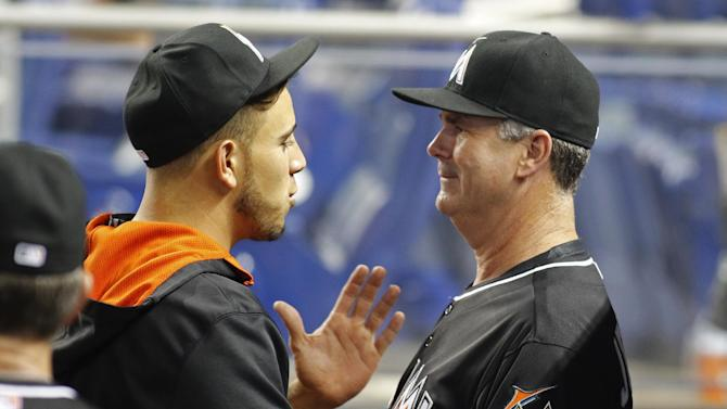 Miami Marlins' manager Dan Jennings, right, speaks with pitcher Jose Fernandez before the Marlins met the Baltimore Orioles in a baseball game in Miami, Saturday, May 23, 2015. (AP Photo/Joe Skipper)