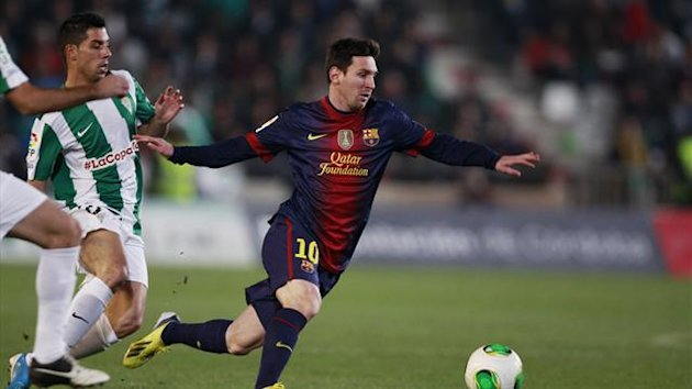 Barcelona's Lionel Messi is challenged by Cordoba's Carlos Caballero