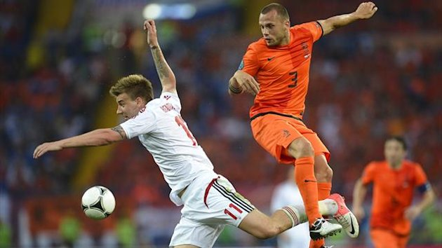 Denmark's Nicklas Bendtner (L) is challenged by Netherlands' John Heitinga at Euro 2012 (Reuters)