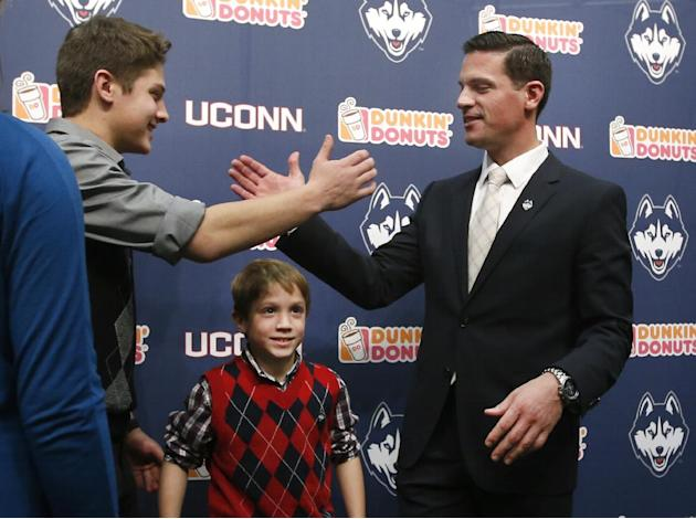 Bob Diaco, right, former Notre Dame defensive coordinator, receives congratulations from his son, Angelo, 16, as his other son, Michael, 9, stands below, after Diaco was introduced as Connecticut'