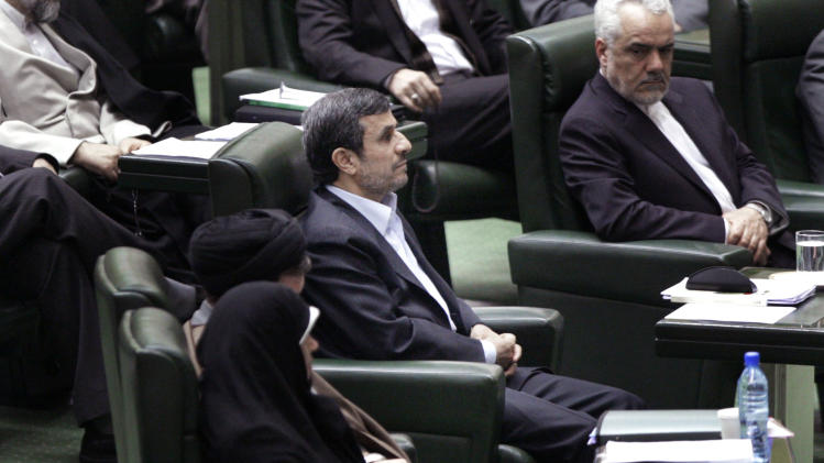 Iranian President Mahmoud Ahmadinejad, center, listens to conservative lawmaker Ali Motahari, unseen, a prominent opponent of the president, as he reads out a series of questions to Ahmadinejad in an open session in parliament in Tehran, Iran, Wednesday, March 14, 2012. Iran's parliament began on Wednesday to question President Mahmoud Ahmadinejad over a long list of accusations, including that he mismanaged the nation's economy and challenged the country's supreme leader. Ahmadinejad is the first president in the country's history to be hauled before the Iranian parliament, a serious blow to his standing in a conflict pitting him against lawmakers. (AP Photo/Vahid Salemi)