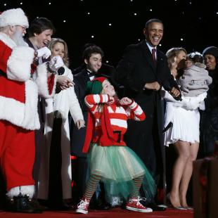 U.S. President Obama dances with entertainers during the National Christmas Tree Lighting ceremony in Washington