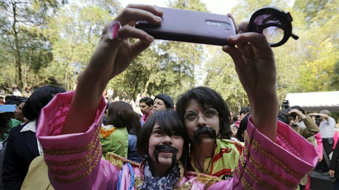 A woman dressed as a member of The Beatles takes a selfie during an attempt to set a Guinness World Record of the largest number of people dressed as The Beatles, at a park in Mexico City