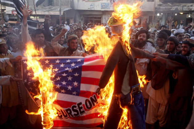 FILE - In this Thursday, Sept. 20, 2012 file photo, Pakistani protesters burn a representation of a U.S. flag and an effigy of U.S. President Barack Obama in the Pakistani border town of Chaman along the Afghanistan border. U.S.-funded ads on Pakistani television include President Barack Obama extolling America's religious tolerance. To many in the Muslim world, this misses the mark in efforts to calm the outrage over a film mocking the Prophet Muhammad. (AP Photo/Matiullah Achakzai, File)