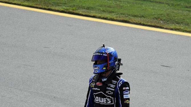 Jimmie Johnson stands in pit road after catching a ride with teammate Dale Earnhardt Jr. after wrecking on the last lap of the NASCAR Sprint Cup auto race at Talladega Superspeedway in Talladega, Ala., Sunday, Oct. 7, 2012. (AP Photo/Dan Lighton)