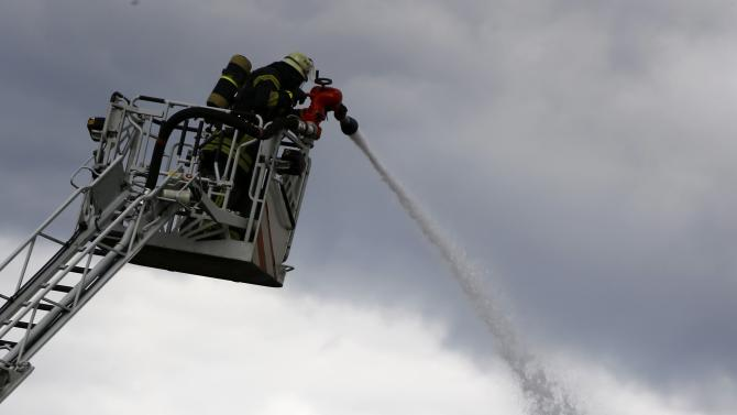 A firefighter uses a water hose to extinguish a building after a fire broke out at a former U.S. airfield in Erlensee