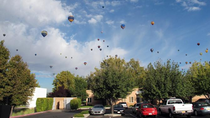 Hot air balloons fill the skies over an office complex in Albuquerque, N.M., on the third day of the Albuquerque International Balloon Fiesta Monday, Oct. 4, 2010. (AP Photo/Tim Korte)