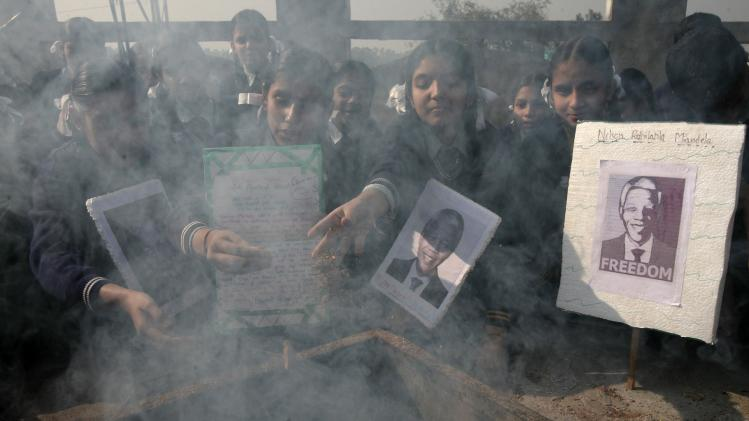 Schoolchildren perform a ritual as they hold portraits of Mandela during a prayer ceremony at a school in Jammu