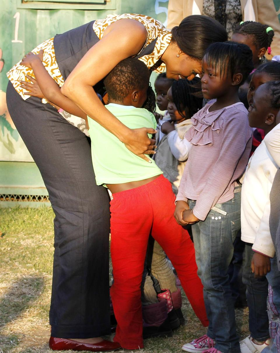 First lady Michelle Obama hugs children during her visit to the Emthonjeni Community Center in Zandspruit Township, Johannesburg, South Africa, Tuesday, June 21, 2011. (AP Photo/Charles Dharapak, Pool)