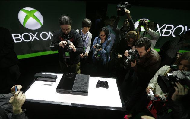 Photographers crowd around Microsoft Corp.'s next-generation Xbox One entertainment and gaming console system after it was officially revealed, Tuesday, May 21, 2013, at an event in Redmond, Wash. It'