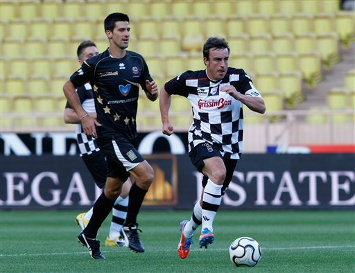 Fernando Alonso of Formula One Drivers Team, right, dribbles past Novak Djokovic of Monaco of Star Team for the Children, right, during a charity soccer match against Formula One Drivers Team, at the