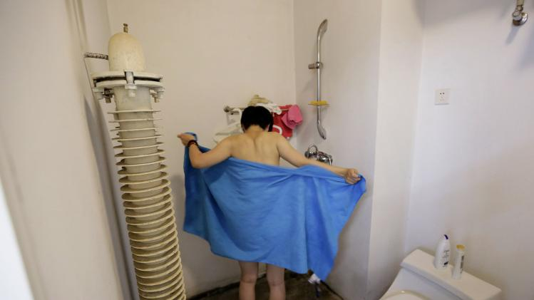 Chinese artist Zhou tries to wrap herself with a bath towel after a day's work at Beijing Art Now Gallery, in Beijing