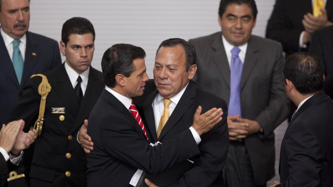 Mexico's President Enrique Pena Nieto, front left, embraces President of the Democratic Revolution Party (PRD) Jesus Zambrano during an event to sign an agreement with the three major political parties that would create two new national television channels and form a powerful independent regulatory commission along the lines of the U.S. Federal Communications Commission, at the Technological Museum in Mexico City, Monday, March 11, 2013. Pena Nieto on Monday proposed a sweeping overhaul of the weak and chaotic regulations that have allowed the world's richest man and the largest Spanish-language media empire to exert near-total control of Mexico's lucrative telephone and television markets. (AP Photo/Alexandre Meneghini)