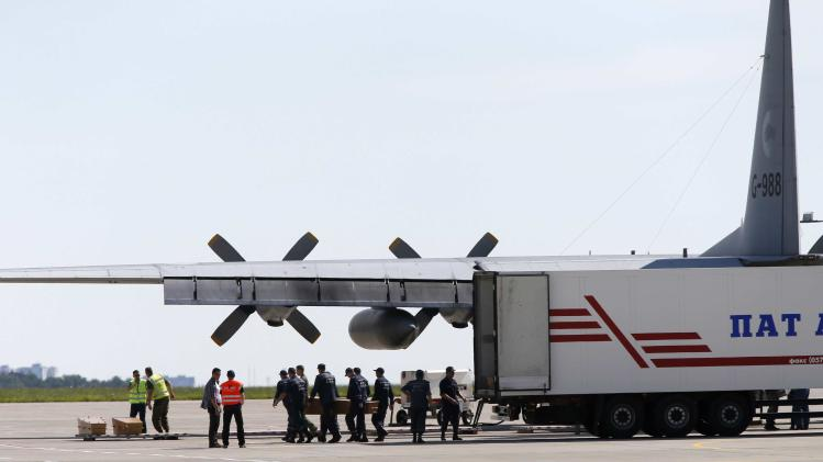 People load coffins carrying some of remains of Malaysia Airlines MH17 victims to a transport plane at Kharkiv airport