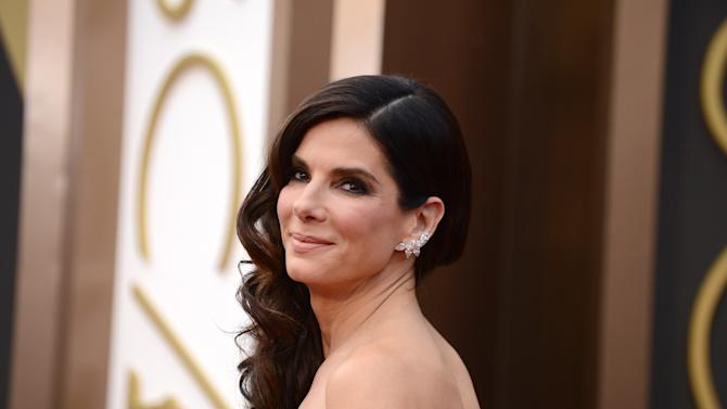 """FILE - In this March 2, 2014 file photo, Sandra Bullock arrives at the Oscars at the Dolby Theatre, in Los Angeles. Bullock's encounter with a stalker in her home reads like a scene from a scary movie in newly released documents, painting a portrait of an obsessed fan who described himself as her """"husband."""" Bullock, who has portrayed brave, strong women on screen, took quick action, locking the door and summoning police. (Photo by Jordan Strauss/Invision/AP, file)"""