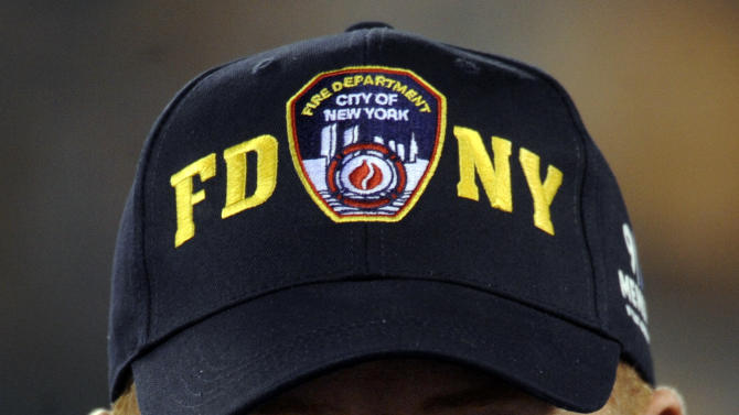 Dallas Cowboys head coach Jason Garrett wears a New York City fire department hat before an NFL football game between the Dallas Cowboys and the New York Jets Sunday, Sept. 11, 2011, in East Rutherford, N.J. (AP Photo/Henny Ray Abrams)