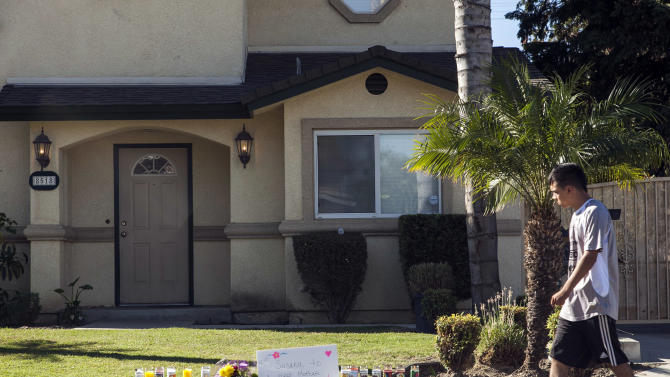 Flowers and votive candles are seen outside the home of the owners of family-owned business, United States Fire Protection Services, in Downey, Calif., Thursday, Oct. 25, 2012. A gunman killed three people and injured two, including a 13-year-old boy, Wednesday in two separate attacks on a family at its suburban Los Angeles business and nearby residence. Police in suburban Los Angeles say the five family members who were shot had been targeted by the gunman.  (AP Photo/Damian Dovarganes)