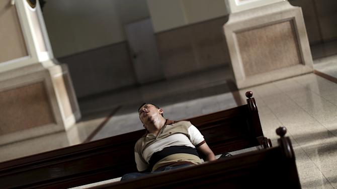 A man sleeps on a bench of the National Cathedral in San Salvador