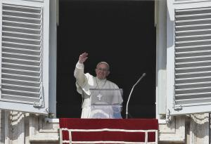 Pope Francis waves to faithful gathered in St. Peter's…