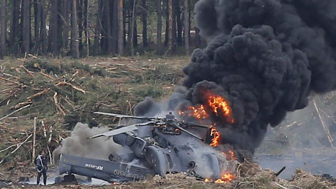 "A pilot stands near a burning Mi-28N helicopter after a hard touchdown during the ""Aviadarts"" military aviation competition near Ryazan"