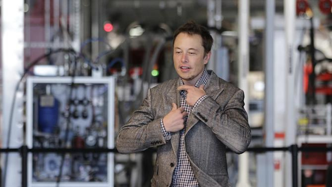 Tesla CEO Elon Musk prepares himself as he walk through the assembly area at the Tesla factory in Fremont, Calif., Friday, June 22, 2012. The first Model S sedan car will be rolling off the assembly line on Friday.  (AP Photo/Paul Sakuma)