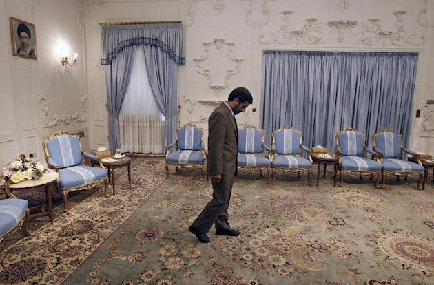 FILE - In this July 11, 2009 file photo, Iranian President Mahmoud Ahmadinejad, waits to receive Omani Foreign Minister Yousuf bin Alawi bin Abdullah at the presidency, in front of a picture of supreme leader Ayatollah Ali Khamenei, in Tehran, Iran. Despite the heavy attention on Iran's external struggles, including sanctions and the shaky rule of critical ally Bashar Assad in Syria, the coming year could be a highly inward-looking one for Iran and Ahmadinejad will be looking ahead for ways to secure some kind of post-presidency political role. (AP Photo/Vahid Salemi, File)