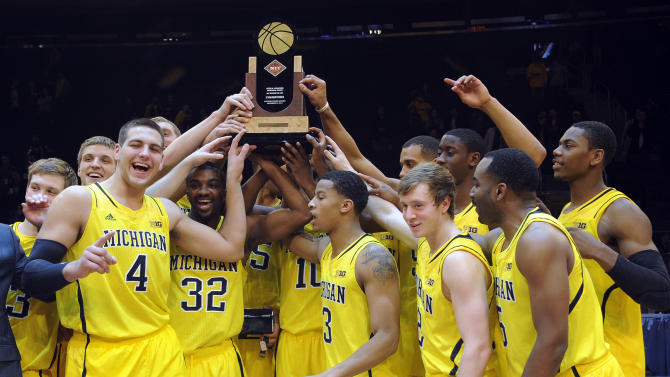 Michigan players celebrate with the trophy after defeating Kansas State, 71-57 in an NCAA college basketball game in the championship of the NIT Season Tip-Off at Madison Square Garden in New York, Friday, Nov. 23, 2012.  (AP Photo/Bill Kostroun)