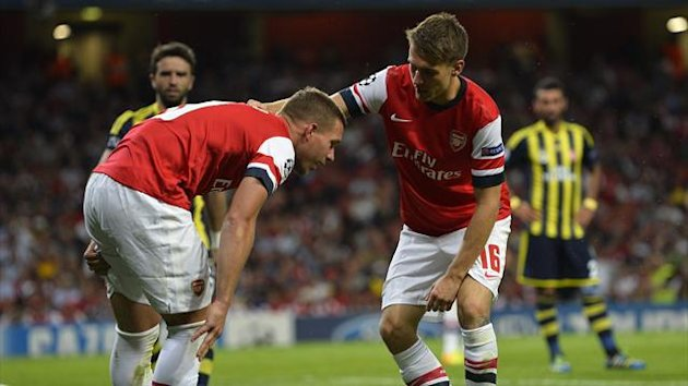 Arsenal's Lukas Podolski (L) is consoled by teammate Aaron Ramsey after pulling his hamstring during their Champions League soccer match against Fenerbahce at the Emirates Stadium in London August 27, 2013 (Reuters)