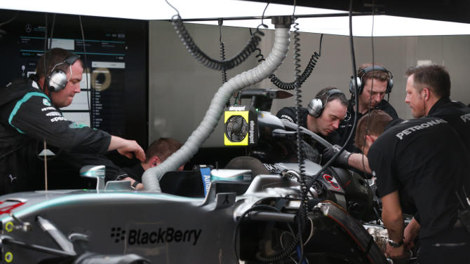 Formula One - F1: Mercedes crew members work on Lewis Hamilton's (not pictured) car in the pit during practice
