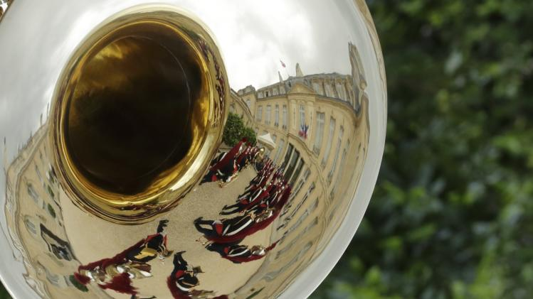 Republican guards are reflected in the tuba of their military fanfare during a ceremony in the courtyard of the Elysee Palace in Paris