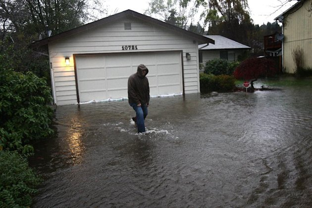 Dan Zarelli walks through a friend's flooded yard near Nathan Hale High School during a significant rainfall on Monday, Nov. 19, 2012. Water running toward Thornton Creek surrounded some homes in the