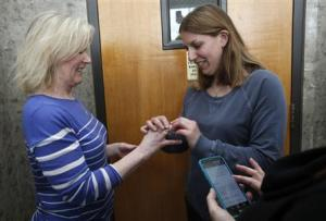 Two women exchange rings during their wedding ceremony in the hallway of the Oakland County Courthouse as the woman officiating the wedding reads the marriage vows from her cell phone