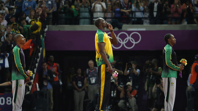 Jamaica's Usain Bolt, center, kisses his gold medal as he stands alongside silver medallist Yohan Blake of Jamaica, right, and bronze medallist Warren Weir of Jamaica during the medal ceremony for the men's 200-meter during the athletics in the Olympic Stadium at the 2012 Summer Olympics, London, Thursday, Aug. 9, 2012. (AP Photo/Matt Dunham)