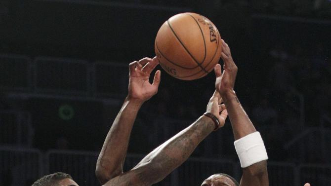 Brooklyn Nets' Joe Johnson (7) and Toronto Raptors' Amir Johnson, left, fight for control of the ball during the first half of an NBA basketball game, Saturday, Nov. 3, 2012, in New York.  (AP Photo/Frank Franklin II)