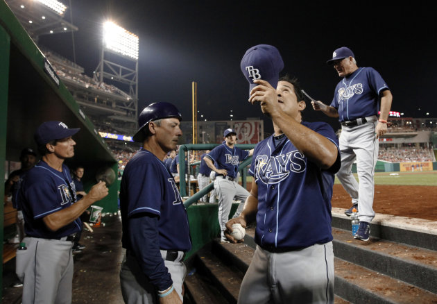 Ejected Tampa Bay Rays relief pitcher Joel Peralta tips his hat as he comes off the field, with manager Joe Maddon, right, as pitching coach Jim Hickey, left, and third base coach Tom Foley watch during the eighth inning of a baseball game against the Washington Nationals at Nationals Park on Tuesday, June 19, 2012, in Washington. The Rays won 5-4. (AP Photo/Alex Brandon)
