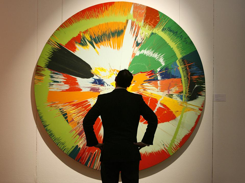 "FILE - In this Tuesday, Jan. 29, 2008 file photo, a Sotheby's employee looks at Damien Hirst's ""Beautiful, Shattered, Mellow, Exploding, Paint-filled Balloons Painting"" at the auction house in London. (AP Photo/Akira Suemori)"
