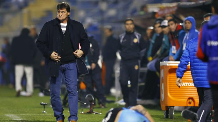 Chile's Universidad Catolica head coach Falcioni walks next to one of his tumbled player during their Copa Sudamericana match against Uruguay's River Plate in Santiago