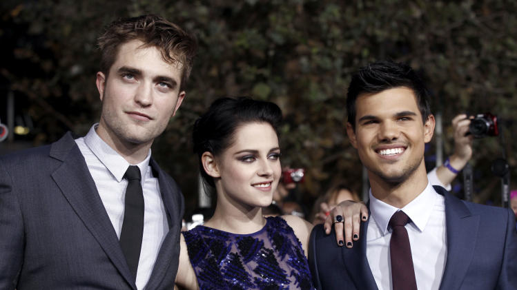 "Robert Pattinson, left, Kristen Stewart, center, and Taylor Lautner arrive at the world premiere of ""The Twilight Saga: Breaking Dawn - Part 1"" on Monday, Nov. 14, 2011, in Los Angeles. (AP Photo/Matt Sayles)"