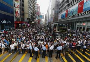 Anti-Occupy Central protesters stand behind a police cordon on Nathan Road at Hong Kong's Mongkok shopping district