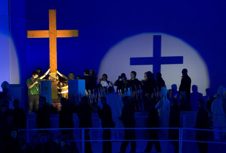Pilgrims hold onto the World Youth Day Cross, also known as the Pilgrim Cross, given to the youth by the late Pope John Paul II, during the inaugural World Youth Day Mass on Copacabana beach in Rio de Janeiro, Brazil, Tuesday, July 23, 2013. (AP Photo/Silvia Izquierdo)