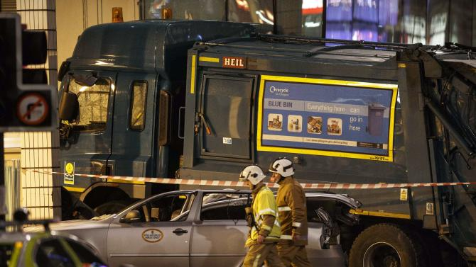 Rescue services personnel walk past a refuse truck that crashed into pedestrians in George Square, Glasgow