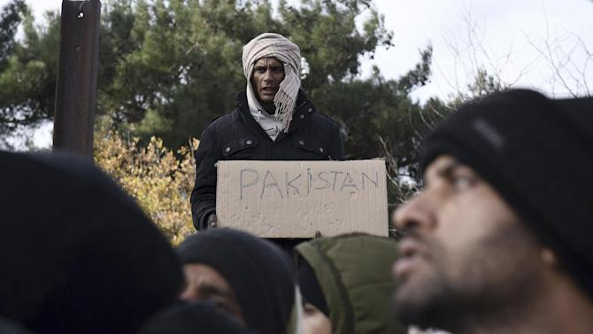 Stranded migrants from Pakistan, who are demanding to be allowed to cross the Greek-Macedonian border, protest near the northern Greek village of Idomeni, Monday, Nov. 30, 2015. Hundreds of migrants are stranded on the Greek side after Macedonia blocked access to citizens of countries that are not being fast-tracked for asylum in the European Union. Macedonia erected a fence on its southern border with neighboring Greece in order to prevent illegal crossings by migrants. (AP Photo/Giannis Papanikos)