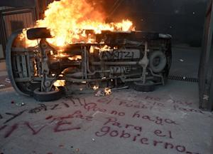 "A car burns next to a graffiti reading ""If there …"