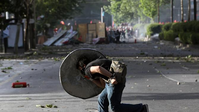 "A protester takes cover during clashes with security forces in Ankara, Turkey, Sunday, June 2, 2013. Turkey's prime minister Recep Tayyip Erdogan on Sunday rejected claims that he is a ""dictator,"" dismissing protesters as an extremist fringe, even as thousands returned to the landmark Istanbul square that has become the site of the fiercest anti-government outburst in years. (AP Photo/Burhan Ozbilici)"