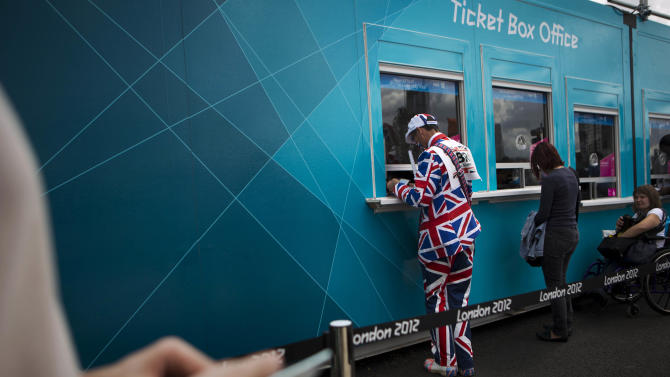 In this Sunday, July 29, 2012 photo, visitors buy tickets for the Olympic Park at the 2012 Summer Olympics, in London. (AP Photo/Emilio Morenatti)
