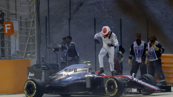 McLaren driver Jenson Button of Britain jumps to leave his car after failing to complete the qualifying session ahead of the Bahrain Formula One Grand Prix at the Formula One Bahrain International Circuit in Sakhir, Bahrain, Saturday, April 18, 2015. The Bahrain Formula One Grand Prix will take place here on Sunday. (AP Photo/Luca Bruno)
