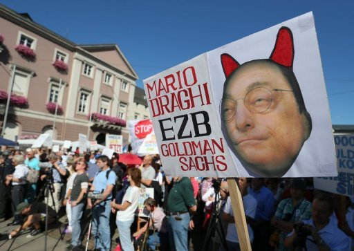"<p>Protesters hold a banner with a devil-like picture of Mario Draghi and a slogan reading ""Don't give ESM a chance"" on September 08 during a demonstration against the European Stability Mechanism (ESM) in Karlsruhe, southern Germany. The ESM is the future firewall for eurozone government rescue funding.</p>"