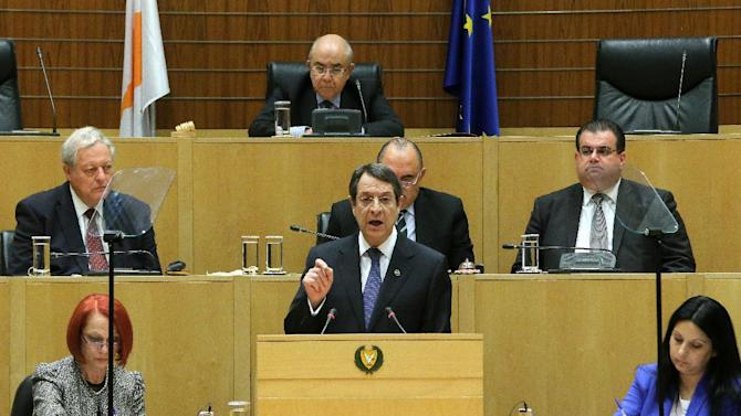 Cyprus' president Nicos Anastasiades, center, speaks to the lawmakers at the Cyprus parliament in divided capital Nicosia, Cyprus, Thursday, Feb. 11, 2016. Anastasiades says peace talks aimed at reunifying the ethnically divided country have marked significant progress on how power will be shared with breakaway Turkish Cypriots and how the economy will function under an envisioned federation. (AP Photo/Petros Karadjias)