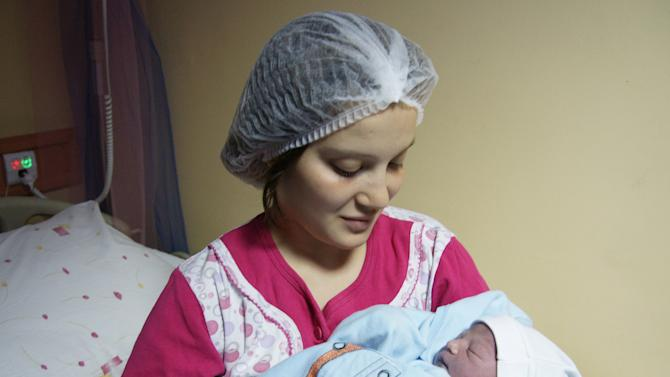 In this photo released by United Nations Population Fund, Gamze Ozkan, 18, holds her new born baby boy, Yusuf Efe, at the Zekai Tahir Burak maternity hospital in Ankara, Turkey, early Monday, Oct. 31, 2011. According to the U.N. Population Fund, Yufuf Efe, son of the unemployed mother and a worker husband, will be one of 7 billion people sharing Earth's land and resources by Monday. (AP Photo/Nezih Tavlas, UNPF) EDITORIAL USE ONLY